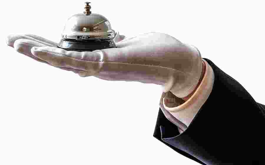 Person in suit with a white glove on holding a shiny service bell over a white background