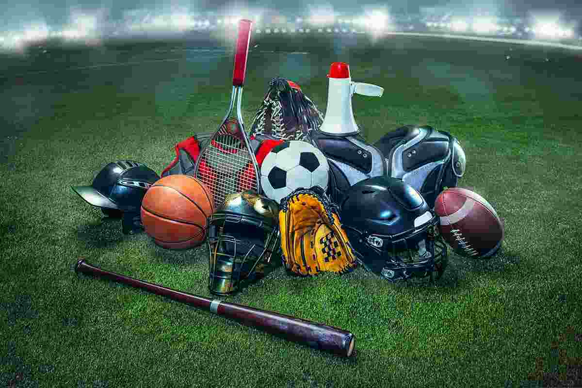Helmets, balls, bats, gloves and other various sporting goods on grass with stadium lighting