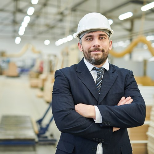 A business man with a hard hat on standing in a warehouse